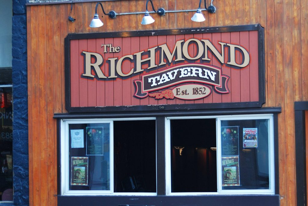 "The outside of the RIchmond Tavern. There's a red sign that says ""The RIchmond"" in gold letters, ""tavern"" in white letters on a black banner, and ""Est. 1852"" in black letters on a gold circle. There's an open window underneath with posters on it."