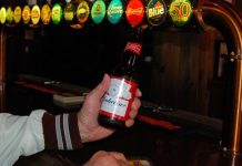 A hand holding a bottle of Budweiser beer in front of a bar with several beer options on tap at the Richmond Tavern.