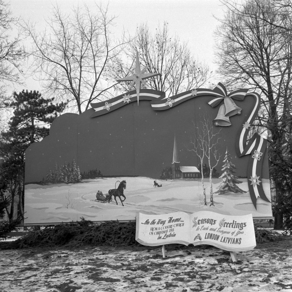"A black and white photograph of a bandshell mural designed for Winter Wonderland in Victoria Park in London, Ontario. There is a picture of a horse and sleigh carrying two people during a winter night. Two bells, a striped ribbon, and Christmas Star are in the top right corner of the mural. There is a sign in front of the church that says ""On the way home from a country church on Christmas Eve in Latvia"" and ""Seasons Greetings to each and everyone of you, London Latvians"