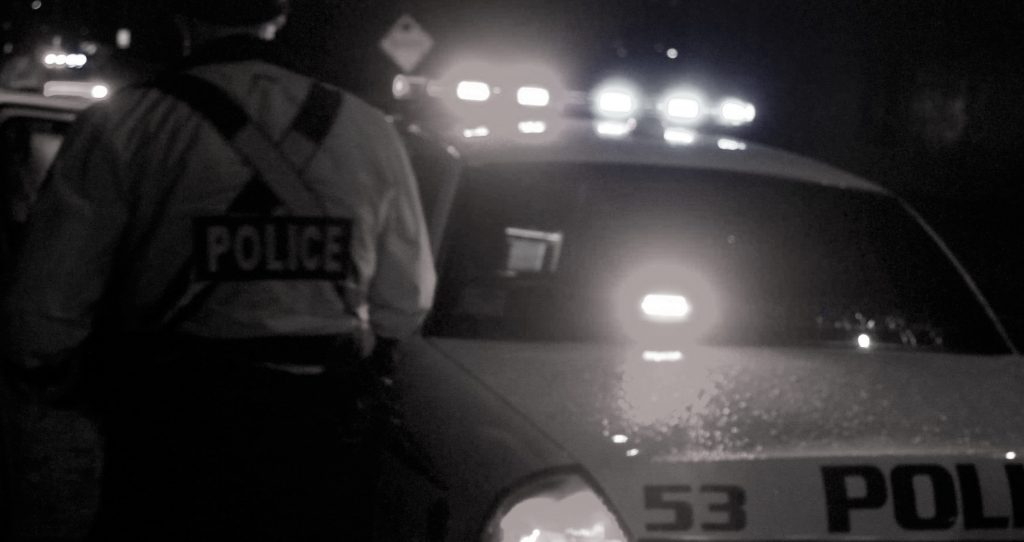 A black and white photograph of a police officer beside a police car with flashing lights.