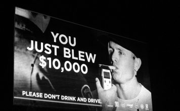 "A black and white photograph of a sign for MADD Canada that says ""You just blew $10,000. Please don't drink and drive."" A man is taking a roadside breath test and an officer is holding the device."