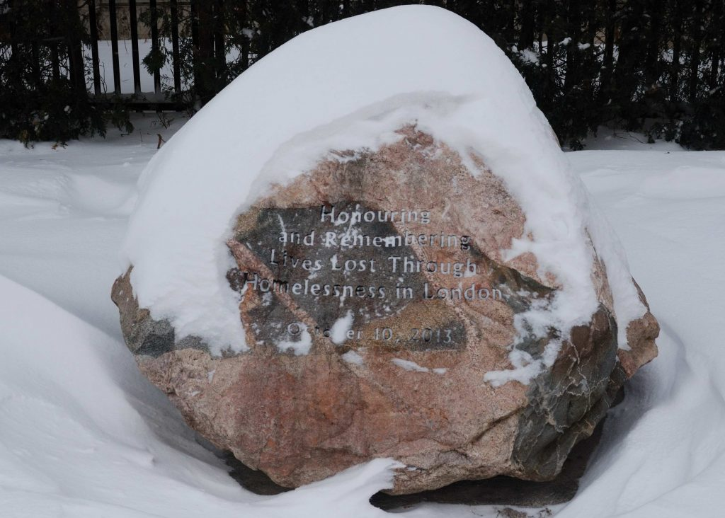 "A memorial stone to honour those who died during their experience from homelessness. The stone says ""Honouring and Remembering Lives Lost Through Homelessness in London."" There is snow on top of the stone and below it. A black fence is in the background."