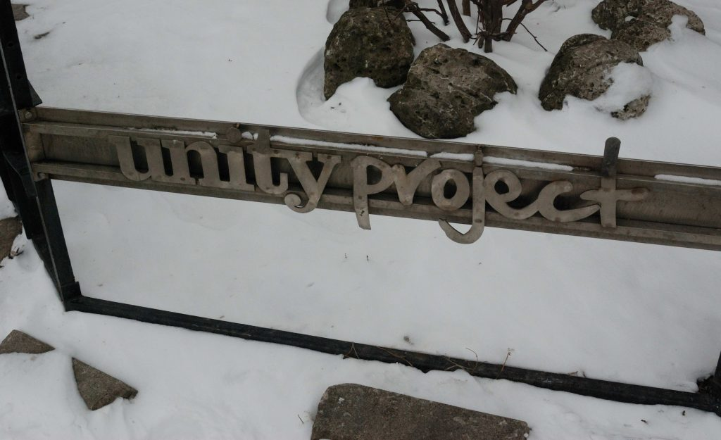 "The metal sign of the Unity Project in London, Ontario. The words ""Unit yProject"" are in silver letters. There are snow and rocks on the ground."
