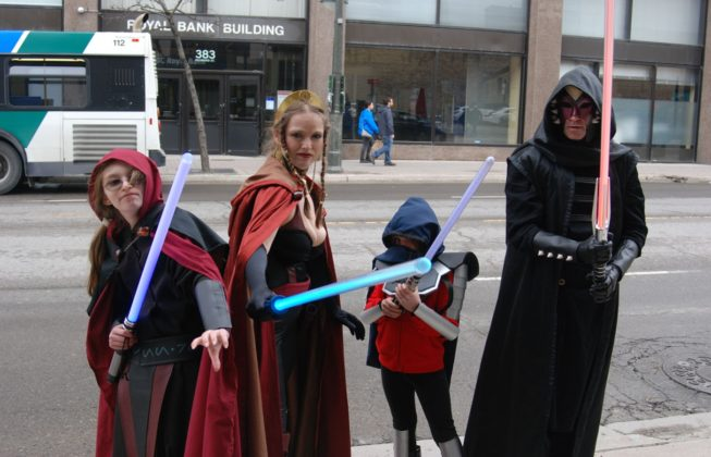 Arwynne Roulston, Wanda Roulston, Lilly Sutherland, and Jeff Roulston as Jedi and Sith from Star Wars during Free Comic Book Day in London, Ontario