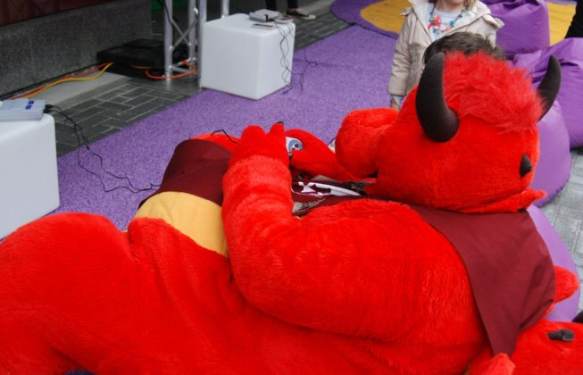 Roary the Dragon from Storybook Gardens playing a game during Free Comic Book Day in London, Ontario