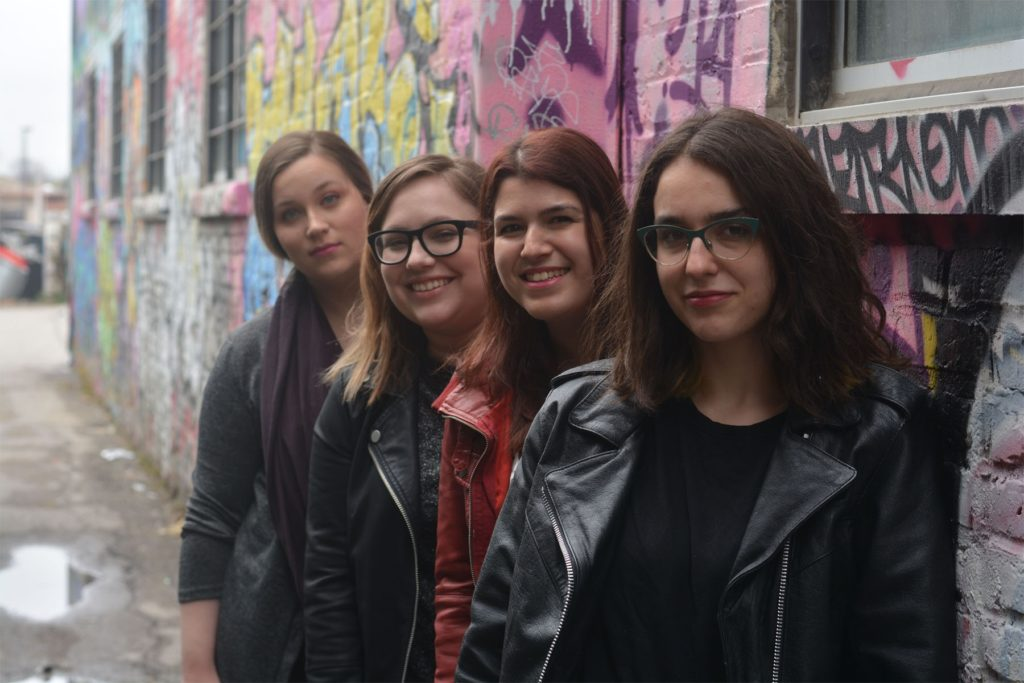Dirt's playwright Stefannie Flannigan, producer Erin J. Walker, and performers Sofia Eidsath and Ashley Fage stand in a row in front of a grafitti-covered wall.