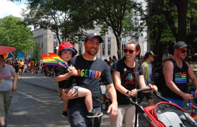 Two people and a baby marching in the 25th Annual London Pride Parade