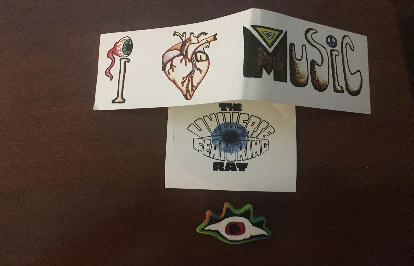 "A sticker that says ""I love music,,"" a sticker that says ""The Universe Featuring Ray"" and an eye pin on a wooden table. All are created by The Universe Featuring Ray"