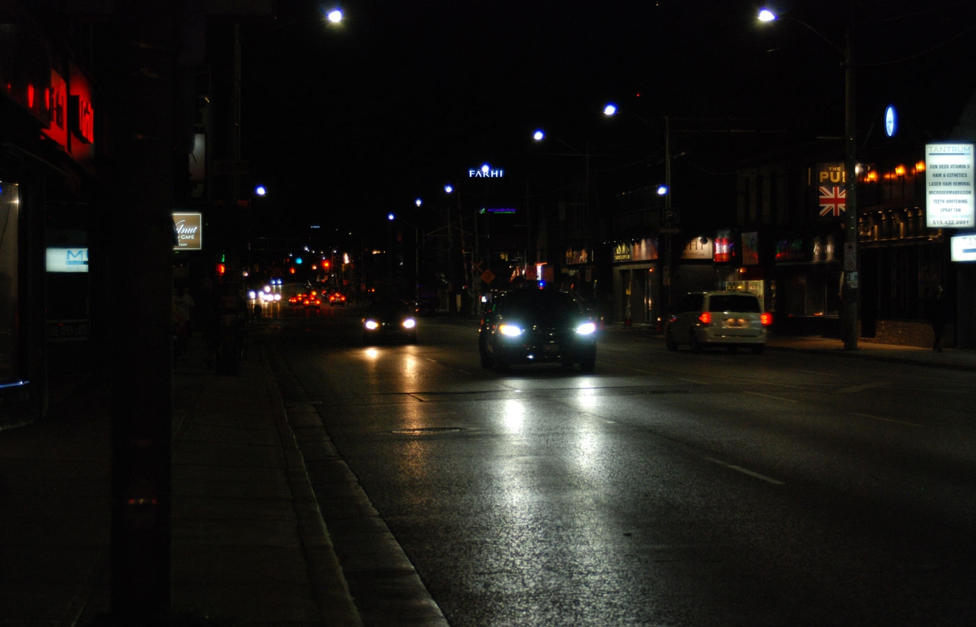 Cars driving down Richmond Street in London, Ontario, at night.