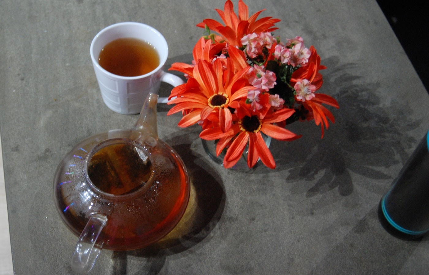 A pot of chai tea, a mug of chai tea, and orange and pink flowers on a table at VRcadia in London, Ontario. There is a grey and teal thermos in the corner.