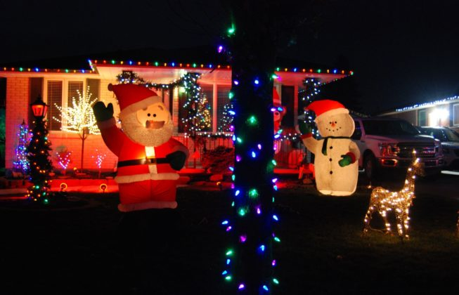An inflatable Santa Claus, an inflatable snowman, and a tree with green and purple Christmas lights on Jena Crescent in London, Ontario