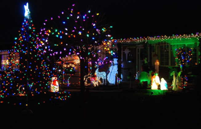 A light display on Jena Crescent in London, Ontario, featuring illuminated snowmen and a tree with purple, green, and blue lights