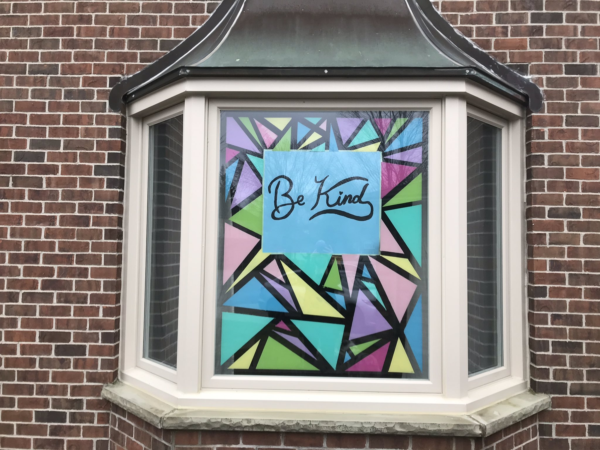 "Artwork in window saying ""be kind"" to spread kindness"