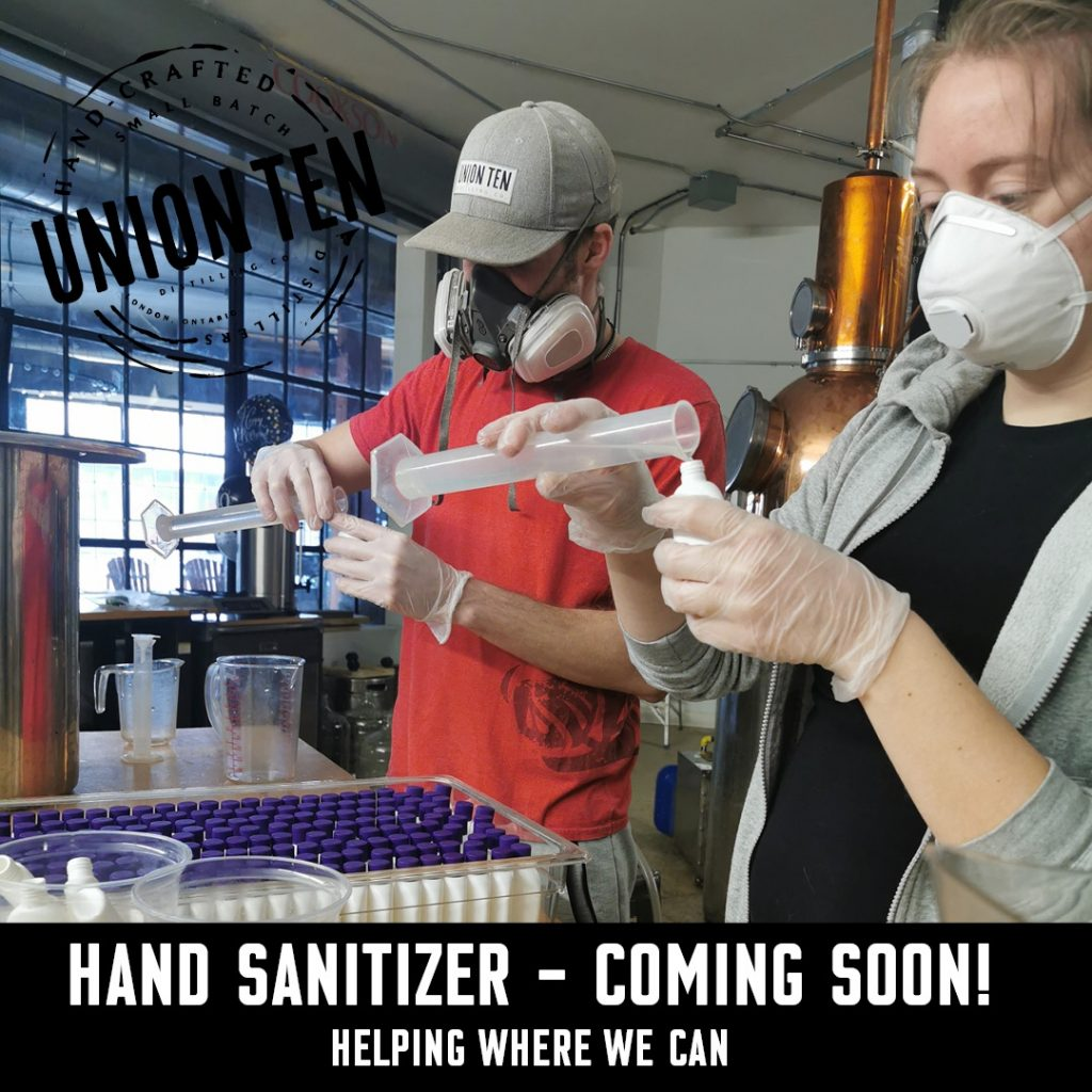 Two people pour hand sanitizer into small bottles.
