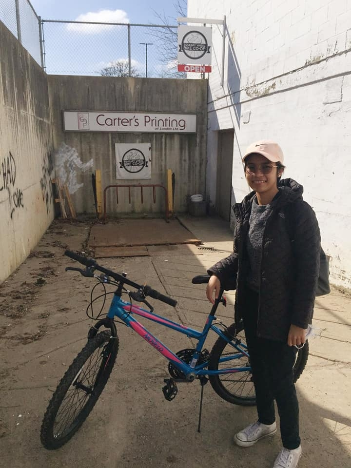 A frontline worker stands next to her new bike from Big Bike Giveaway and Squeaky Wheel Bike Co-op.