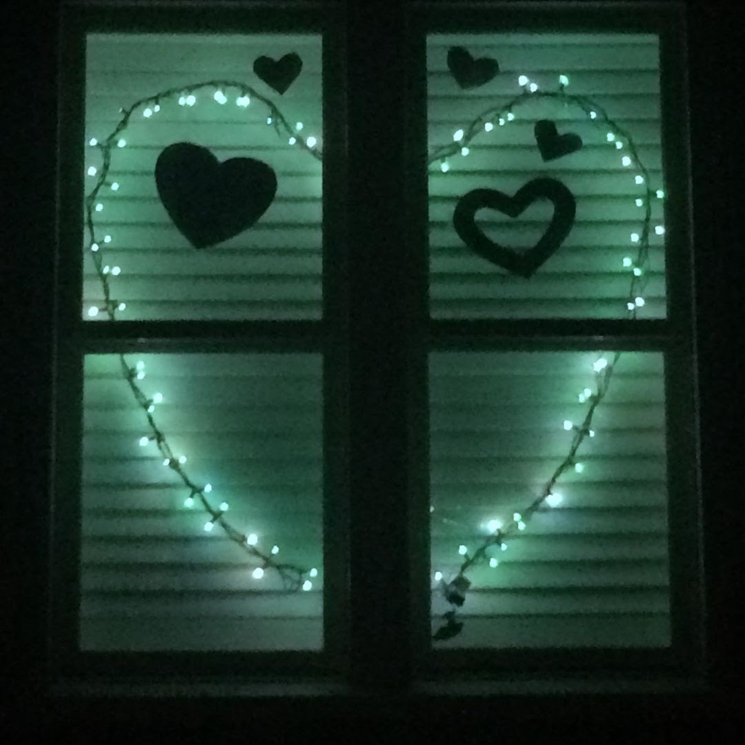 A string of lights in a window form a heart
