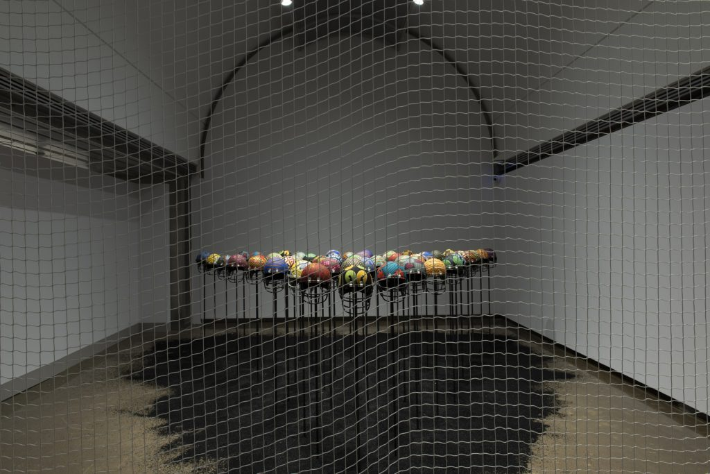 Glorious Bones, 2018-19, repurposed football helmets, African wax prints, faux soil, metal, and Fences, 2019, hockey goal mesh, Courtesy of Georgia Scherman Projects, Photo: Lucas Link Stenning.