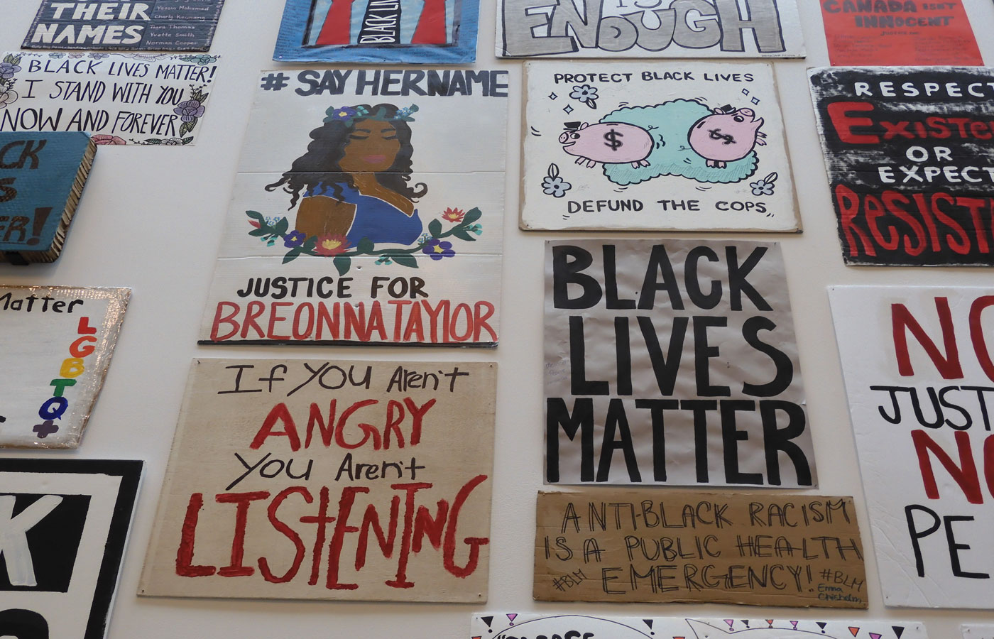 "A variety of Black Lives Matters signs at Museum London in London, Ontario. Messages include ""#SayHerName"" Justice for Breonna Taylor with a drawing o Breonna Taylor, ""Protect Black Lives, defund the cops"" with piggy banks, ""Black Lives Matter,"" ""Anti-Black Racism is a Public Health Emergency"" and ""If you aren't angry, you aren't listening."""