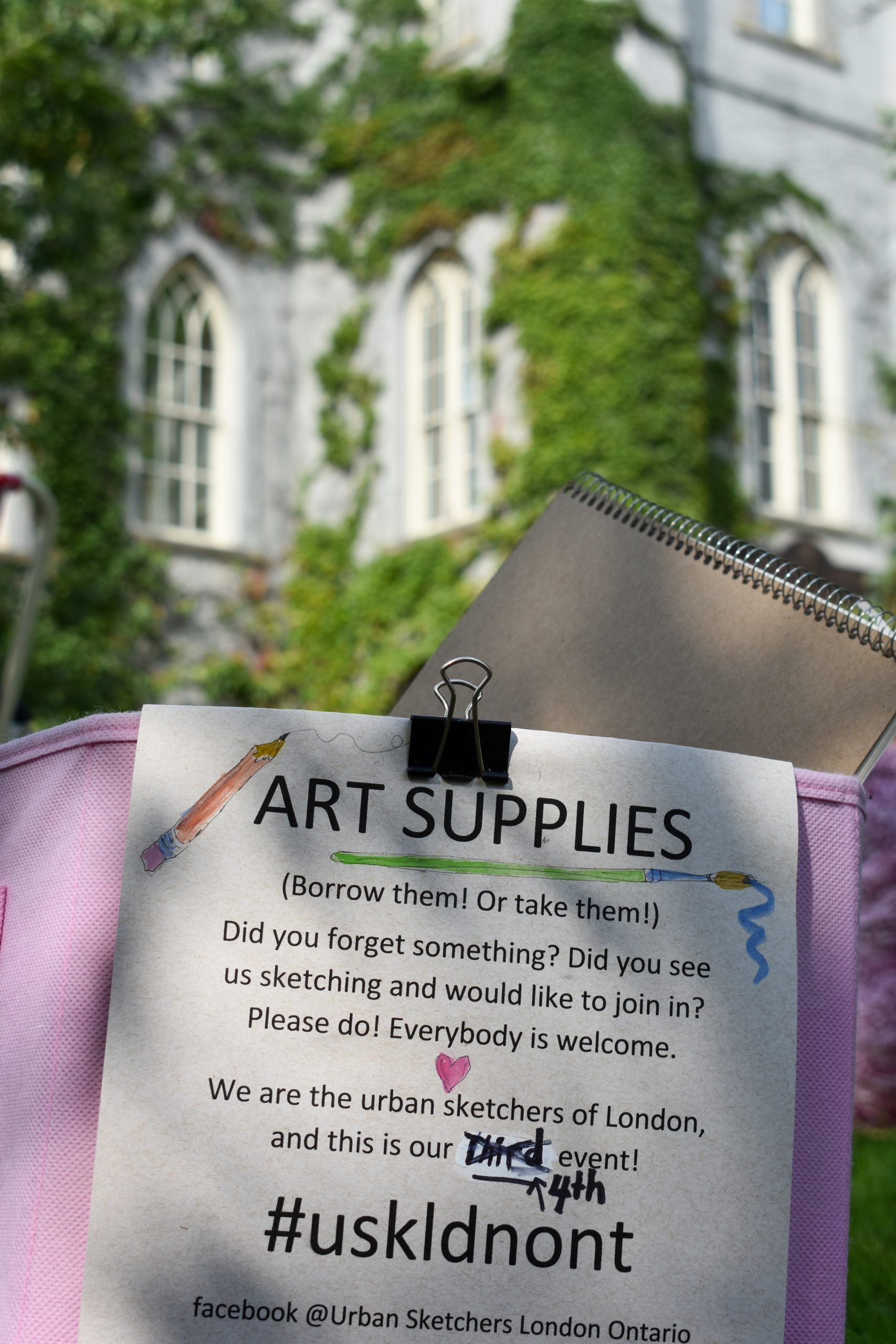 A container of art supplies with a sign welcoming people to join urban sketching