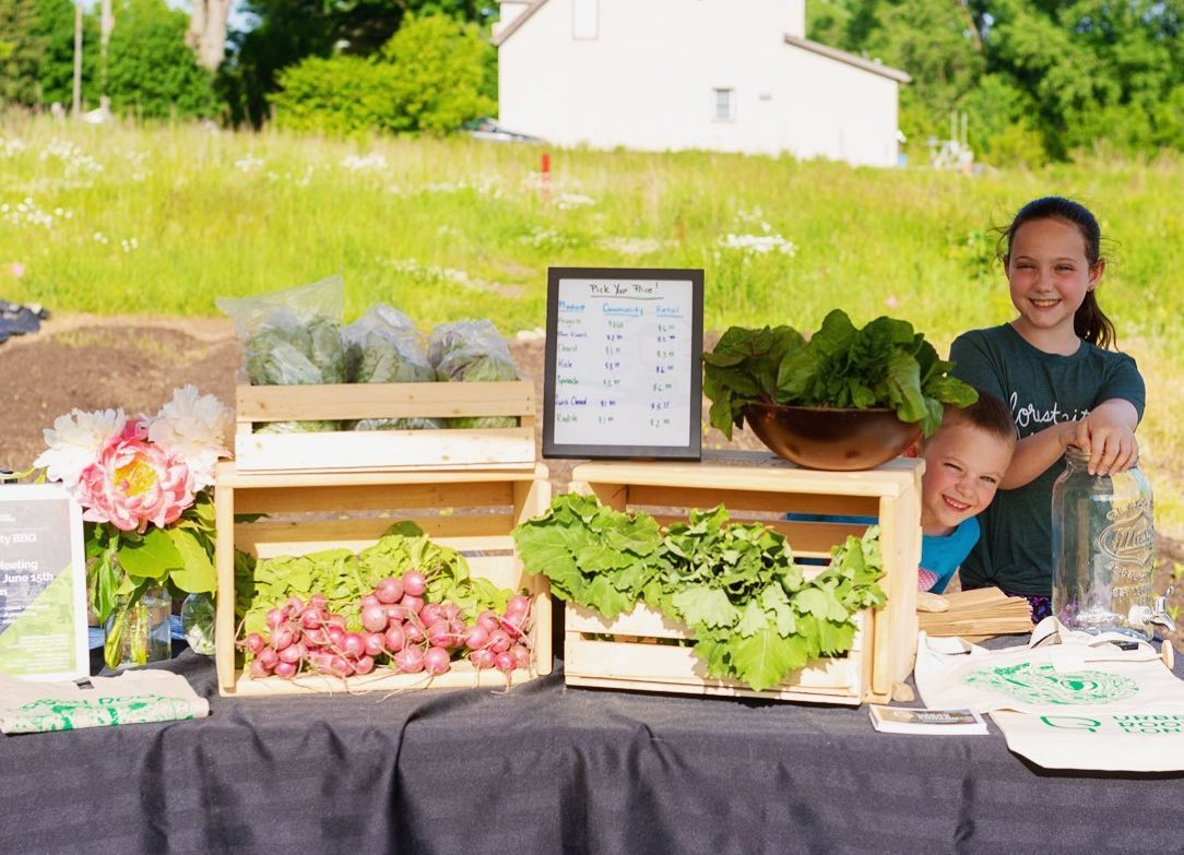 A table full of healthy produce with two young kids smiling
