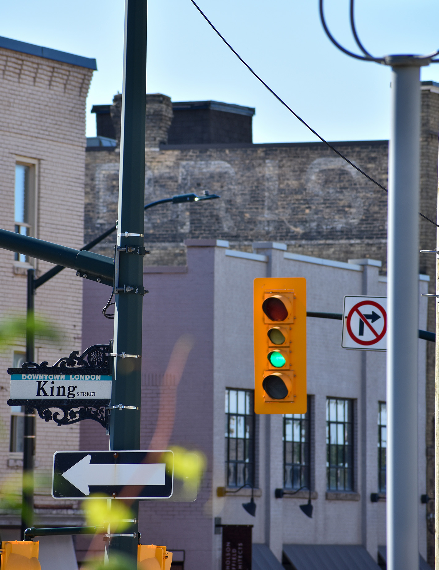 An intersection with a traffic light and street sign that says King. In the background are brick buildings, one has writing on it.