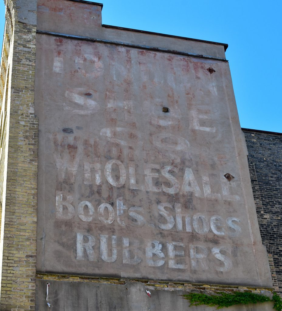 A faded ghost sign says wholesale boots, shoes, and rubbers