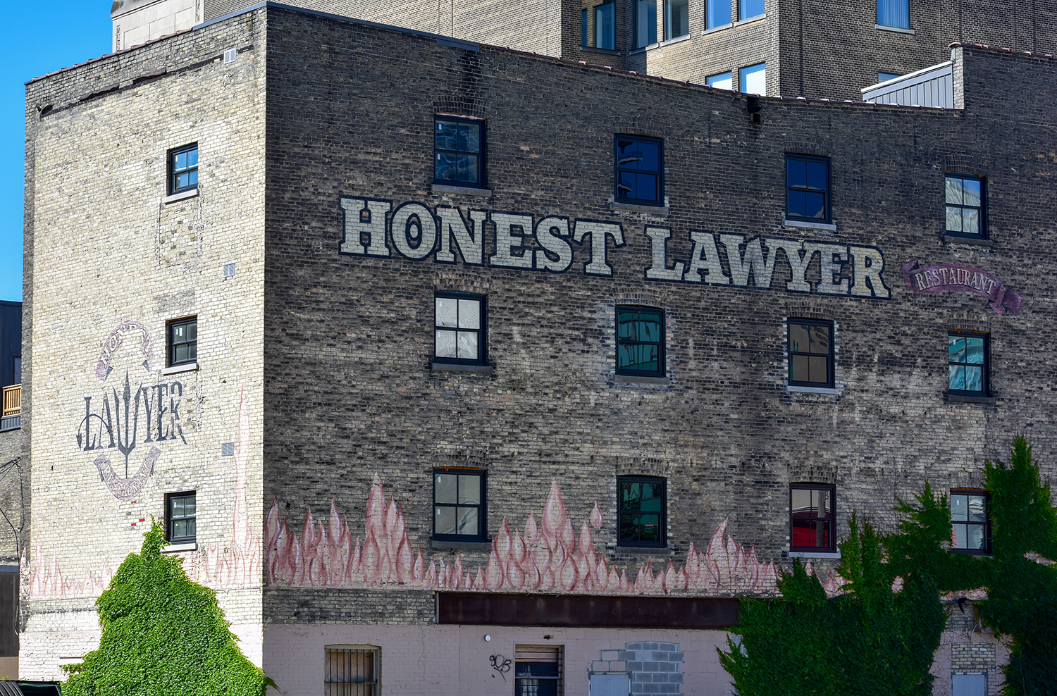 a four story building with a ghost sign that says honest lawyer