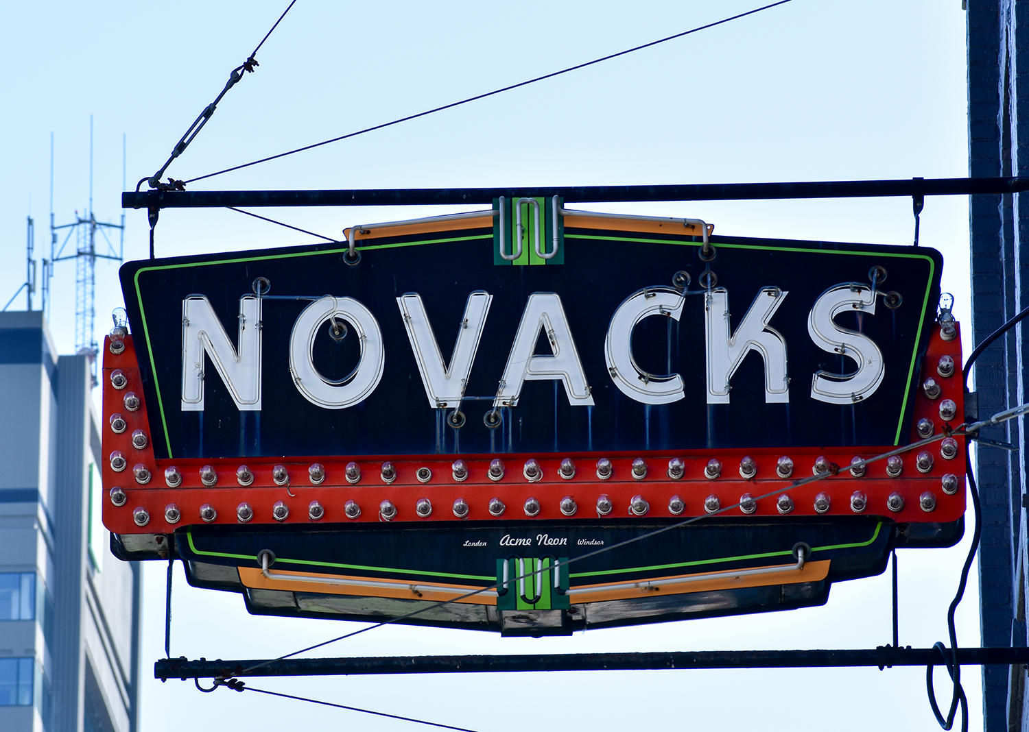 a neon sign in yellow, green, and red that says Novacks