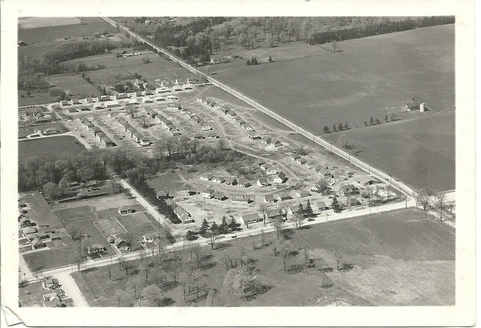 A black and white photo of early Huron Heights, featuring an intersection and a row of houses.