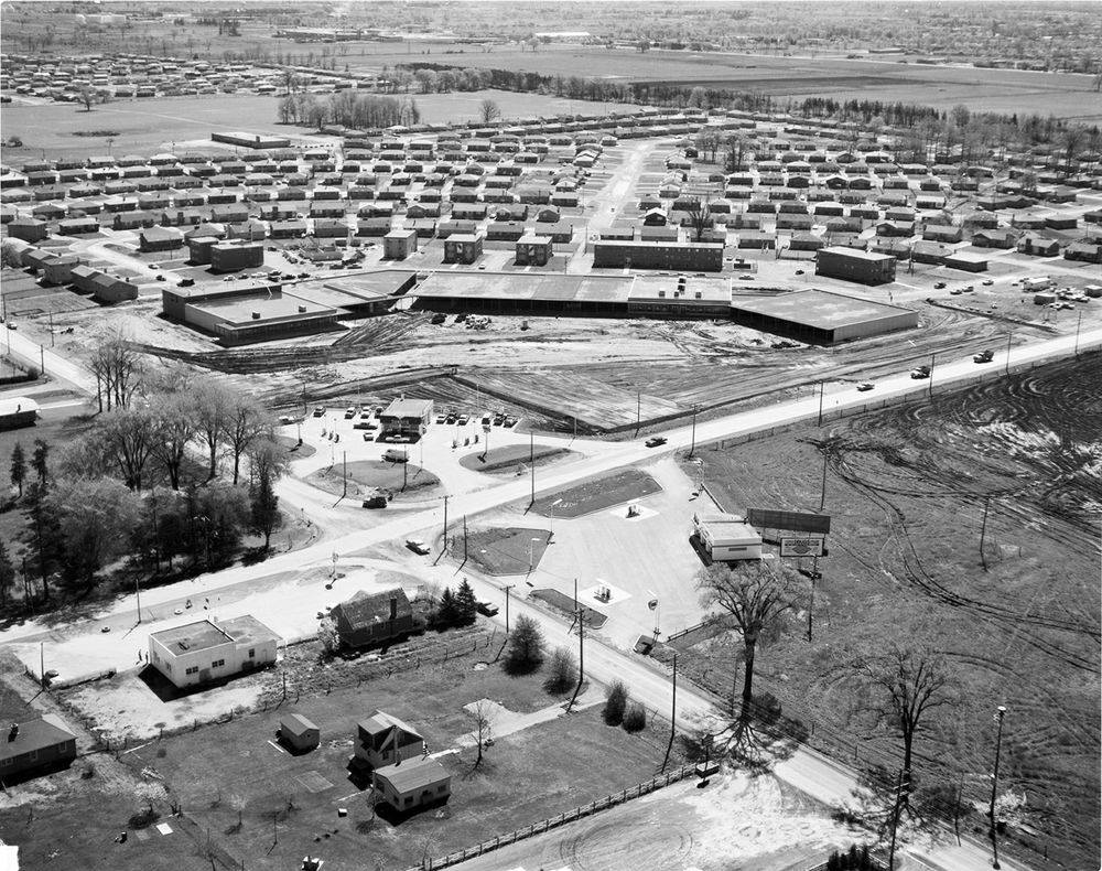 A black and white photo of Huron Heights with a shopping plaza under construction.