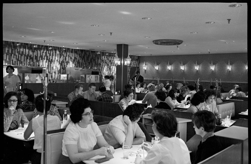 Black and white photo of people sitting at booths.