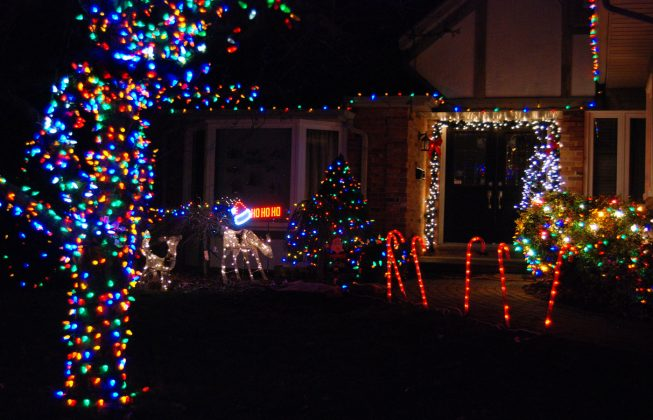 "An illuminated house with holiday displays including lights, deer, a sign with a Santa hat that says ""Ho,ho, ho!"" and candy canes in Masonville in London ON"