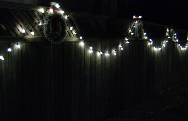 Christmas wreaths and a string of white lights across a fence in Masonville in London, ON