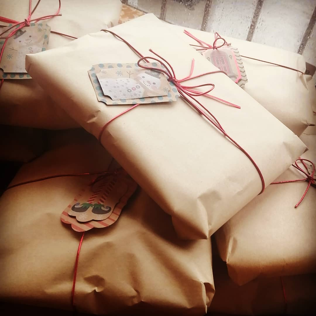 Gifts are wrapped in brown paper with red string and snowman tags.