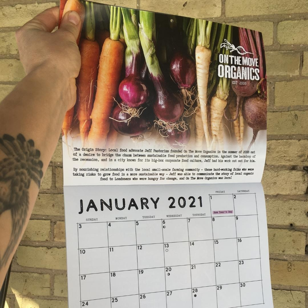 A hand holds up a gift calendar with January 2021 written on it.