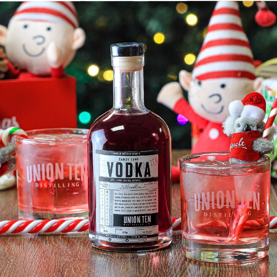 A bottle of red vodka sits between two glasses of red liquid with candy canes and elves in the background.