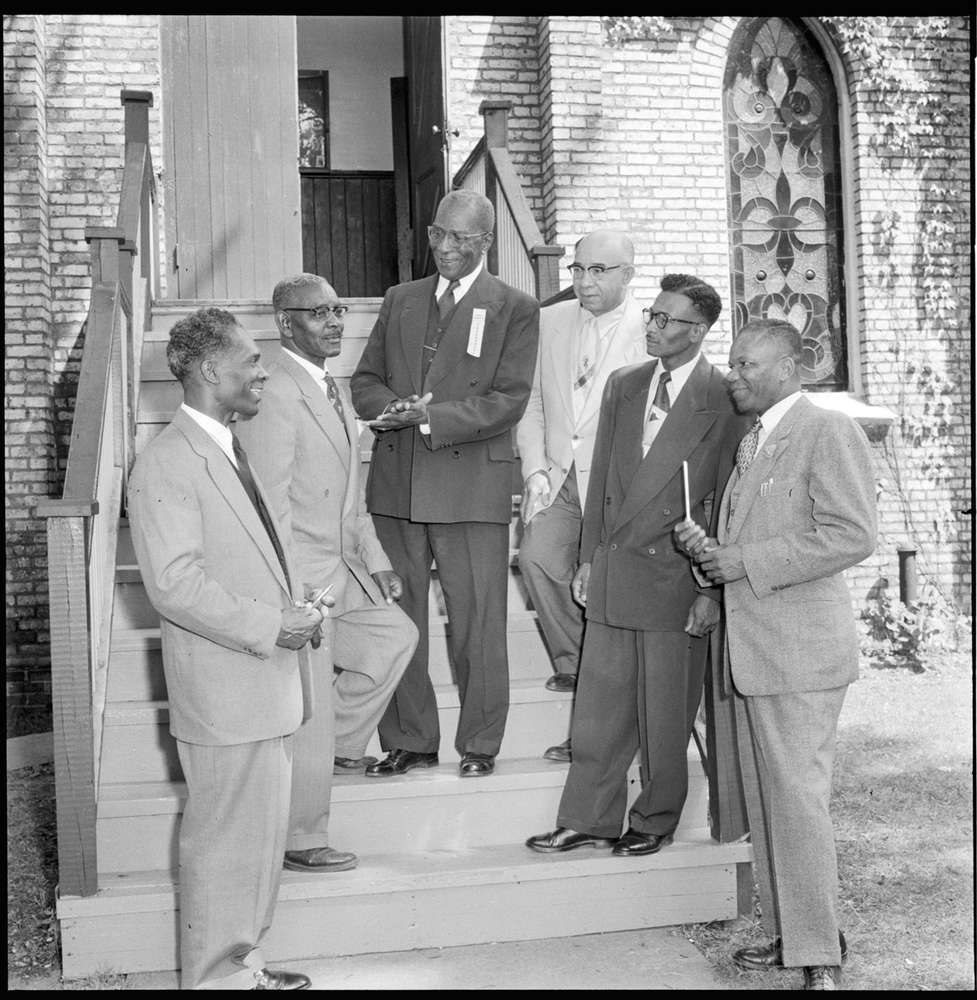 A black and white photo of a group of men, standing on the stairs of a church with stained glass in the background.
