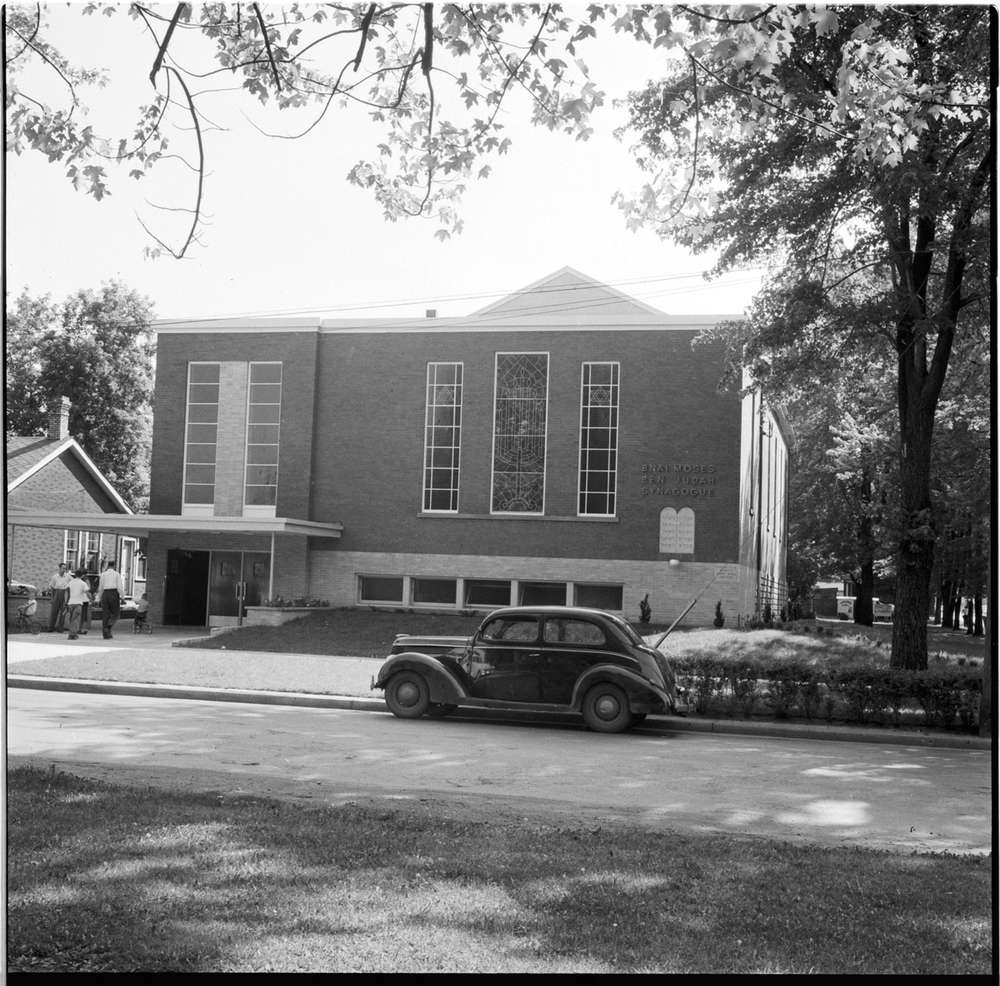 A black and white image of a car parked in front of a brick synagogue in London's SoHo. On the left of the photo, people can be seen entering the building.