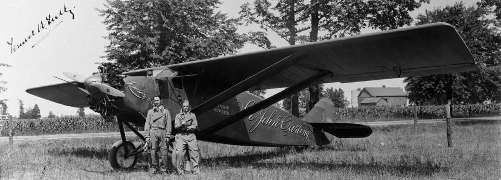 "Two pilots stand in front of a plan that says ""Sir John Carling"" in a black and white photo."