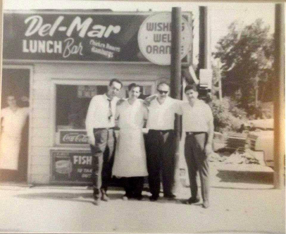 "Four men standing in front of a restaurant with the sign ""Del-Mar Lunch Bar"" with a fifth man leaning in the doorway."