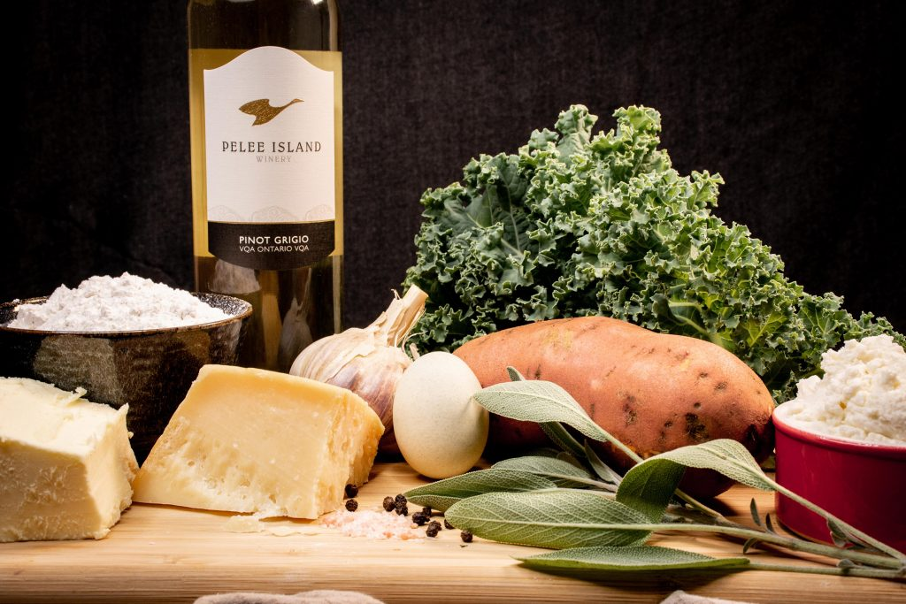 A set of ingredients is displayed, including sweet potatoes, cheese, kale, wine, flour.