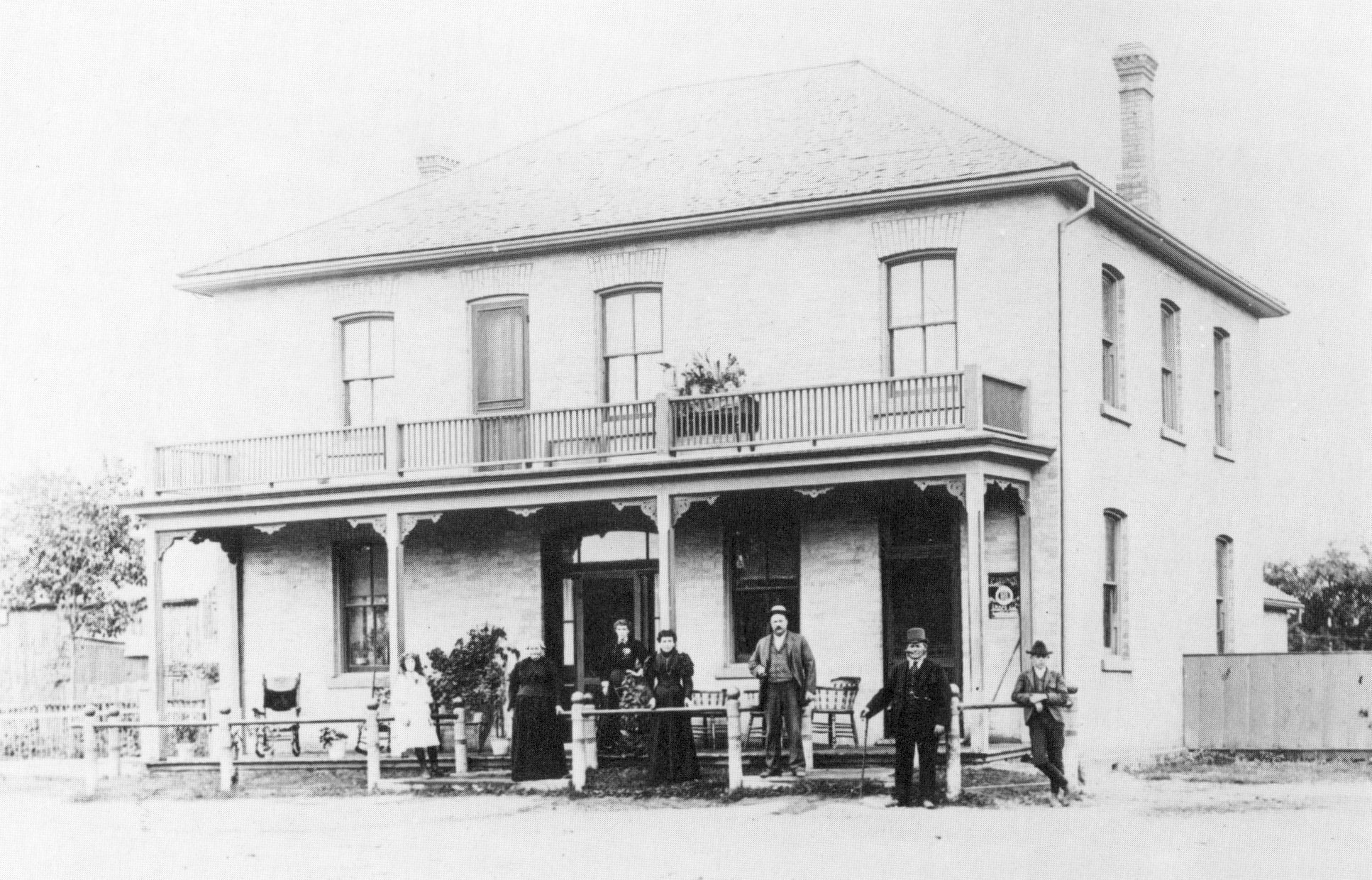 A black and white photo of a two-storey house with several people standing out front.