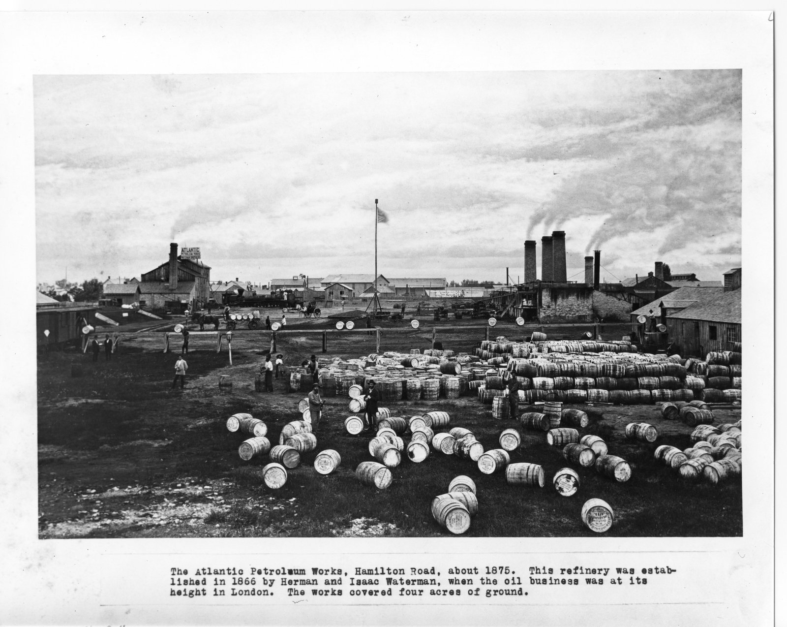 A black and white photo of an industrial yard on Hamilton Road with hundreds of barrels piled up.