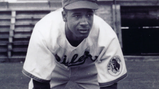 A black and white photo of a baseball player in uniform leaning over his knees.