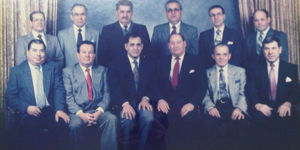 A group of 12 men, all in suits, in two rows. The front row is seated and the back row stands behind them.