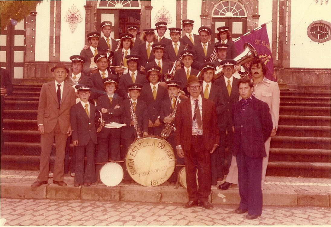 a sepia-toned photograph of a marching band posing on the steps of a building in uniform with their instruments.