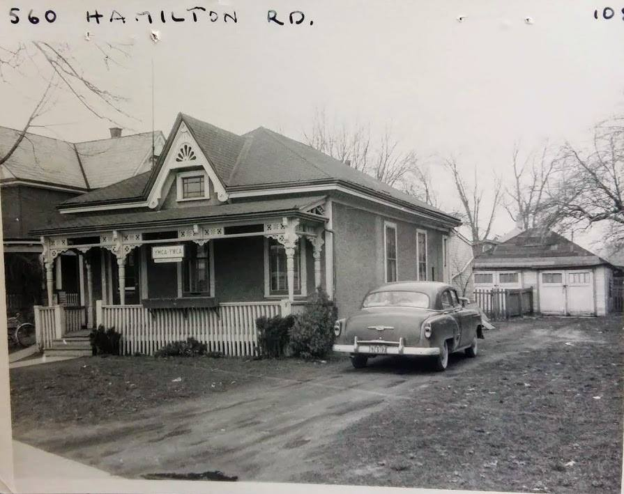 A black and white photo of a house with a sign that says YMCA-YWCA. A car is parked next to the house.