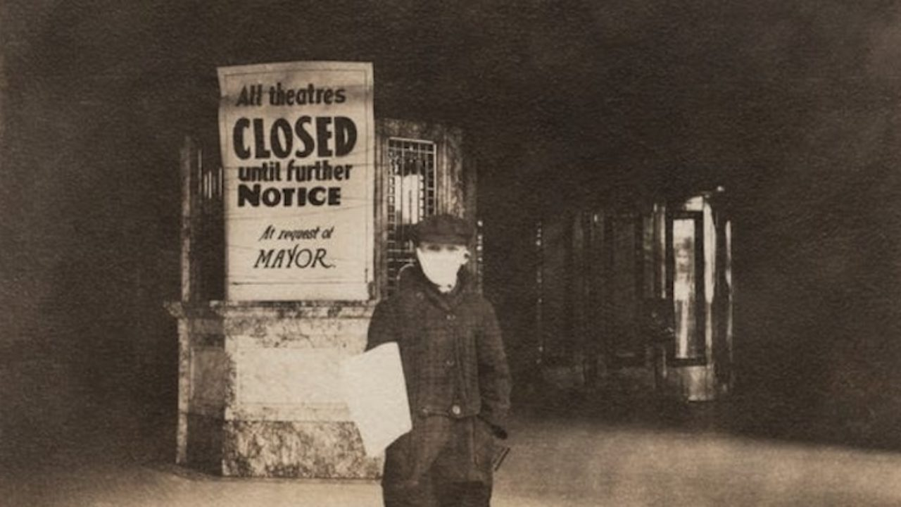 a boy with a face mask stands in front of a theatre with a sign that says all theatres cloesd until further notice at request of mayor