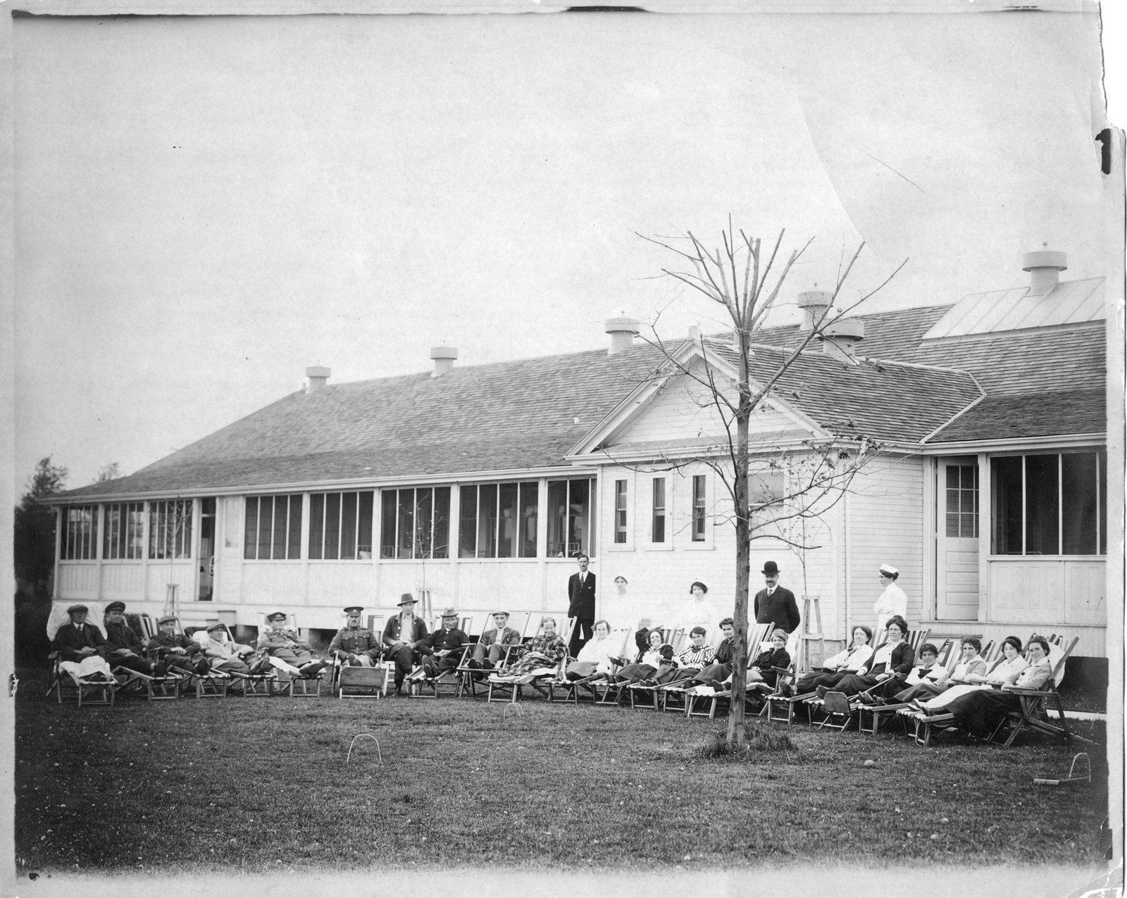 Twnety people sit outside in a row in lawn chairs in front of a medical building. doctors and nurses stand behind them.