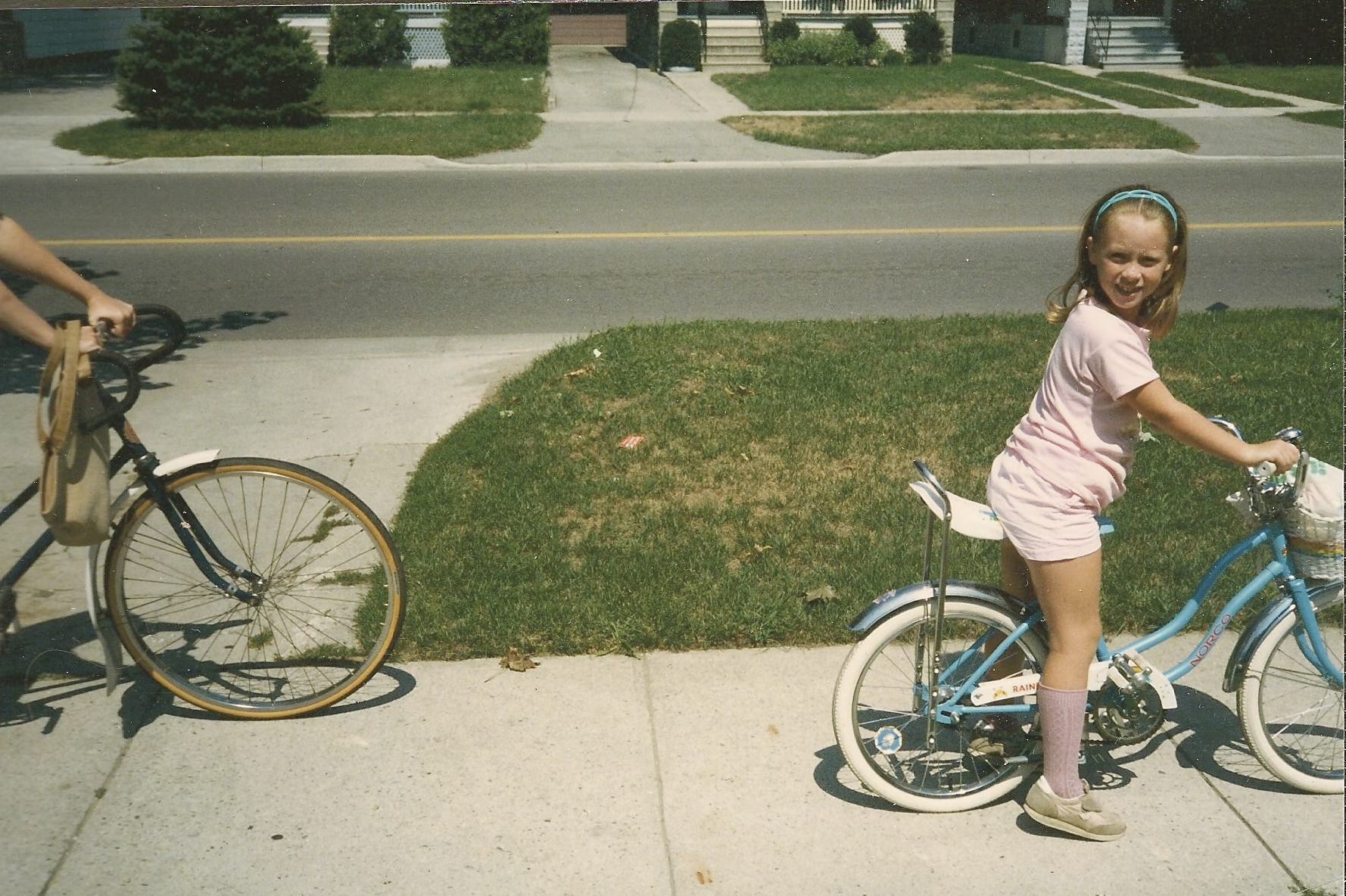 A kid sits on a bicycle in a suburban neighbourhood in the 1980s.